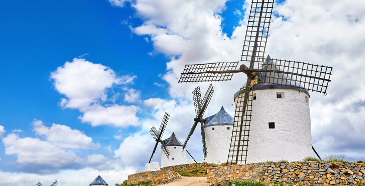 Wind mills at knolls at Consuegra, Toledo region, Castilla La Mancha, Spain. Route of Don Quixote with windmills. Summer landscape with blue sky and clouds. (Wind mills at knolls at Consuegra, Toledo region, Castilla La Mancha, Spain. Route of Don Qui
